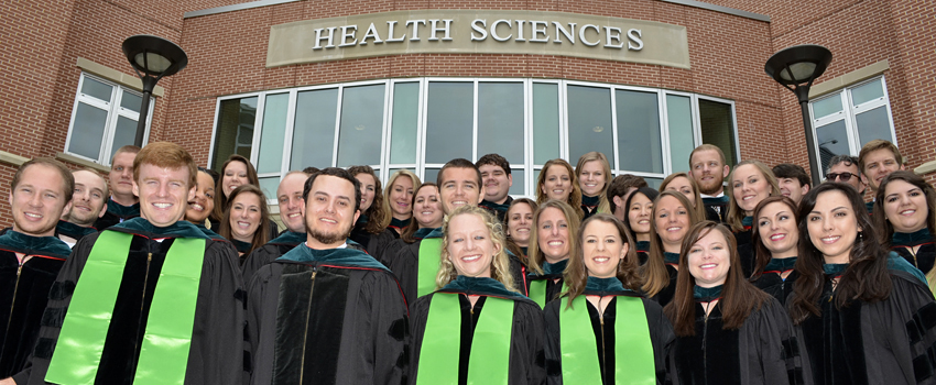 Graduates in their gowns in front of the health sciences building