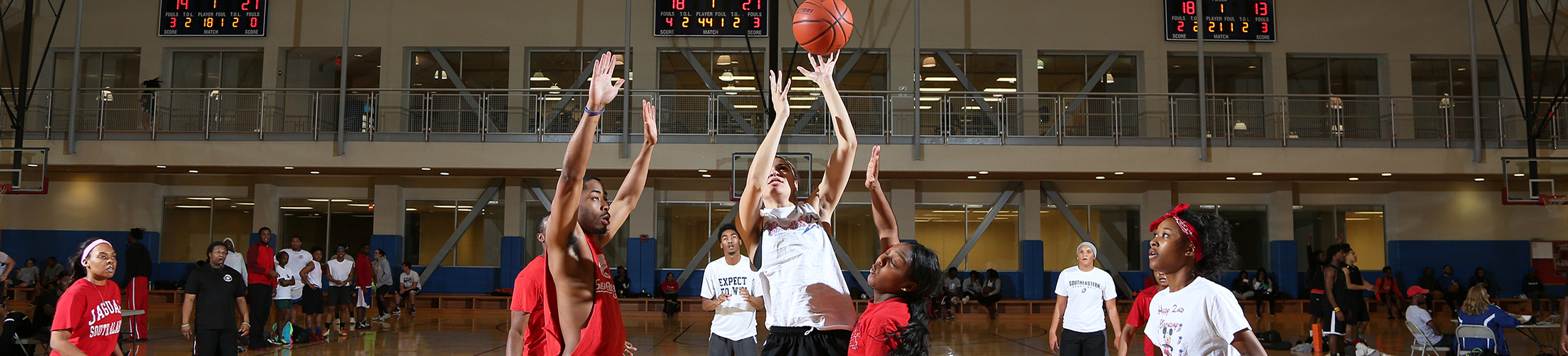 Students playing basketball in campus rec gym.