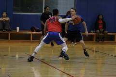 Two male students playing basketball in gym