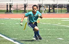 Young boy playing flag football.