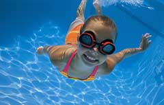 Young girl in goggles swimming