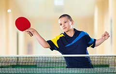 Young boy playing ping pong.