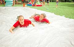 Camp counselors sliding on slip and slide.