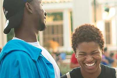 A male and female student laughing outside at a Jaguar Productions event.