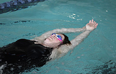 Female swimming on back in pool