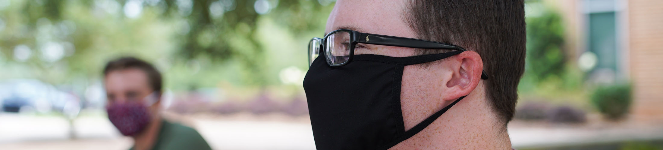 Male student with glasses looking to side with mask on.